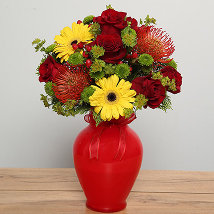 Mixed Flowers Arrangement In Red Glass Vase:
